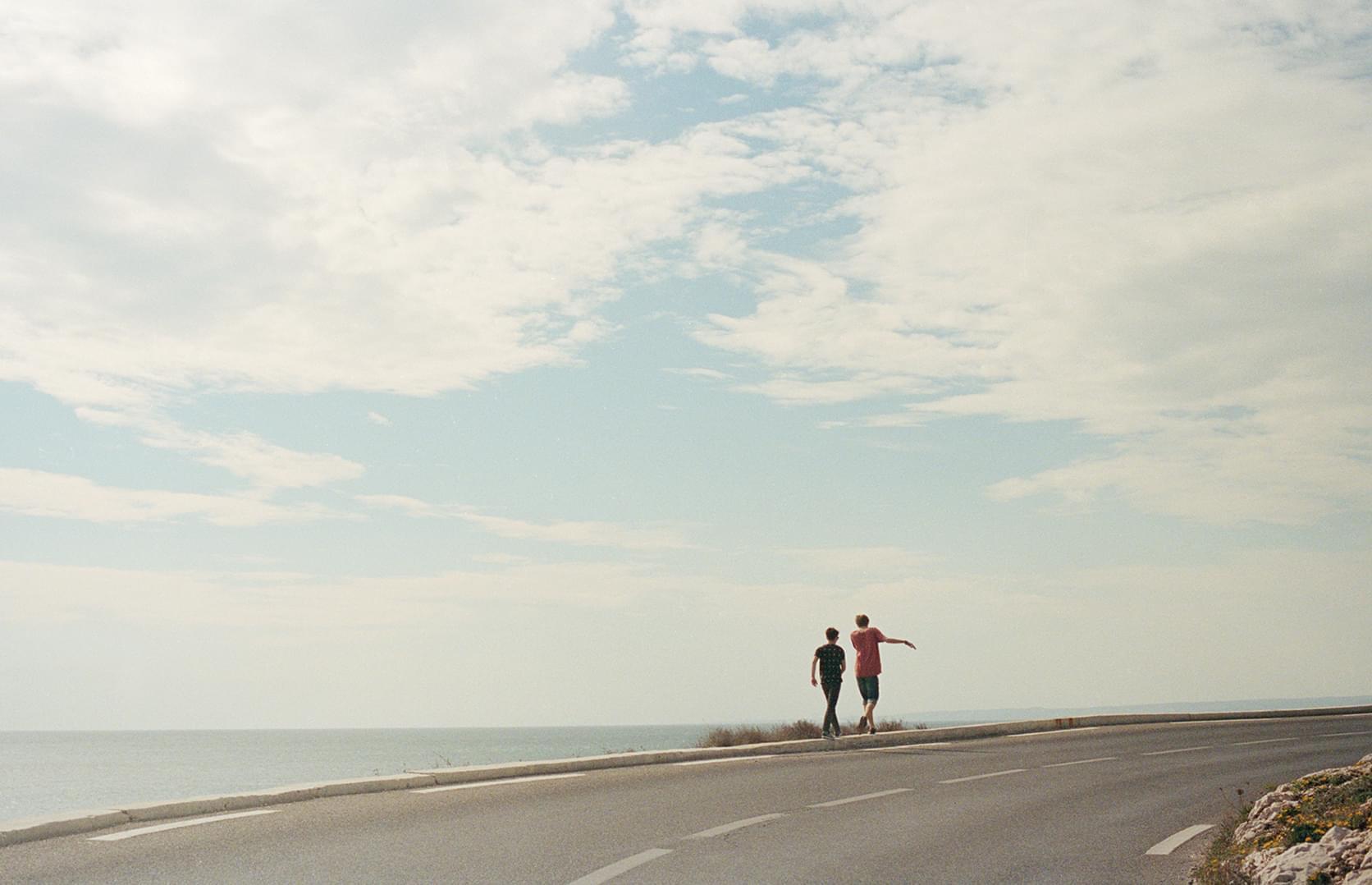 Deux personnes sur une route en bord de mer