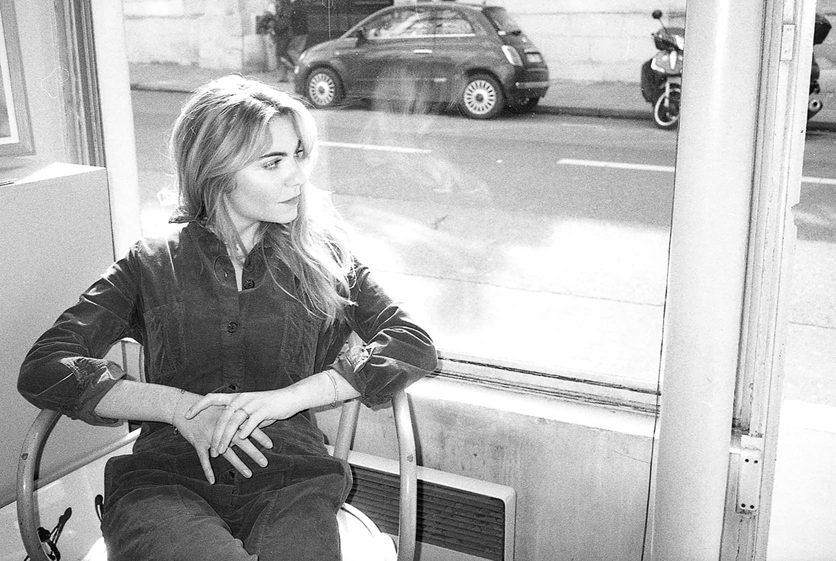 Margaux Avril assise devant une vitrine porte la combinaison Setagaya de Sessùn
